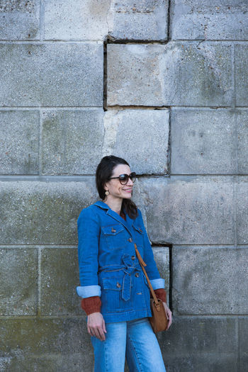 Smiling woman looking away while standing against wall