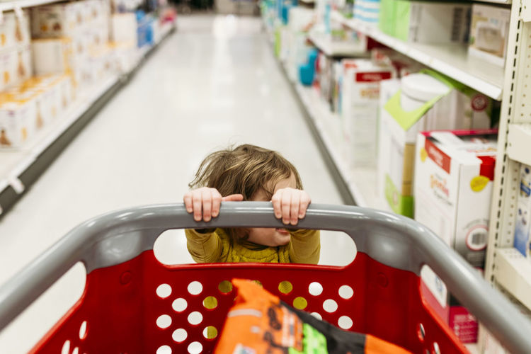 Rear view of boy holding toy at store