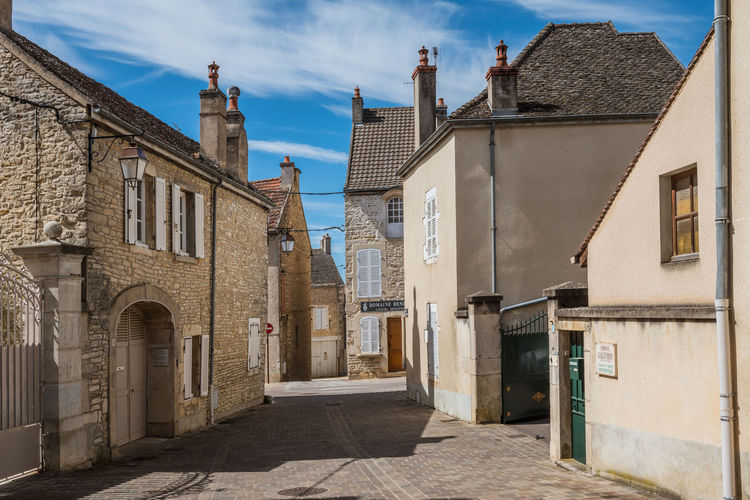 Street amidst buildings in town against sky