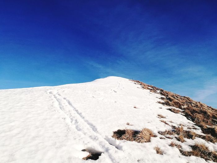 Low angle view of snow covered landscape against blue sky