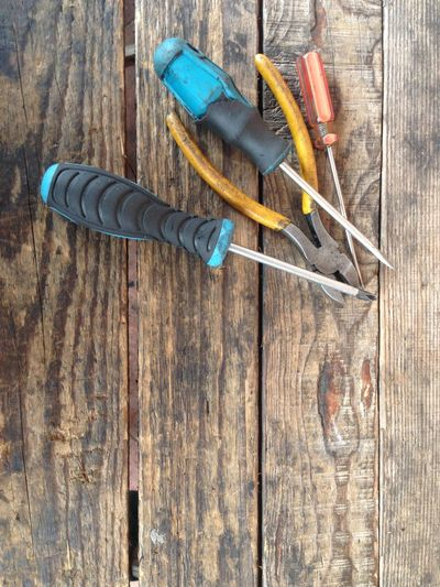 A set of screwdriver and a cutter on the wooden background. Basic Black Blue Close-up Competence Day Dirty Flat Foreman Jobs No People Philips Repair Screwdrivers Skills  Wood - Material Yellow