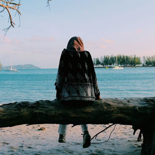 Rear view of woman sitting on fallen tree trunk at beach against sky