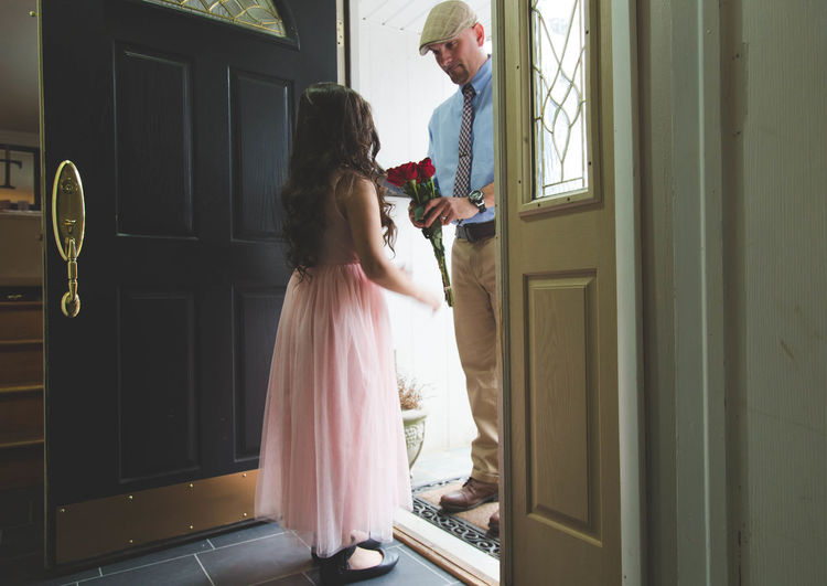 Father Giving Roses To Daughter Wearing Pink Dress At Doorway