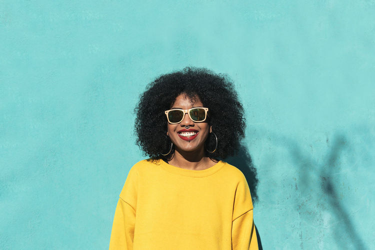 Portrait of smiling young woman wearing sunglasses against standing yellow wall