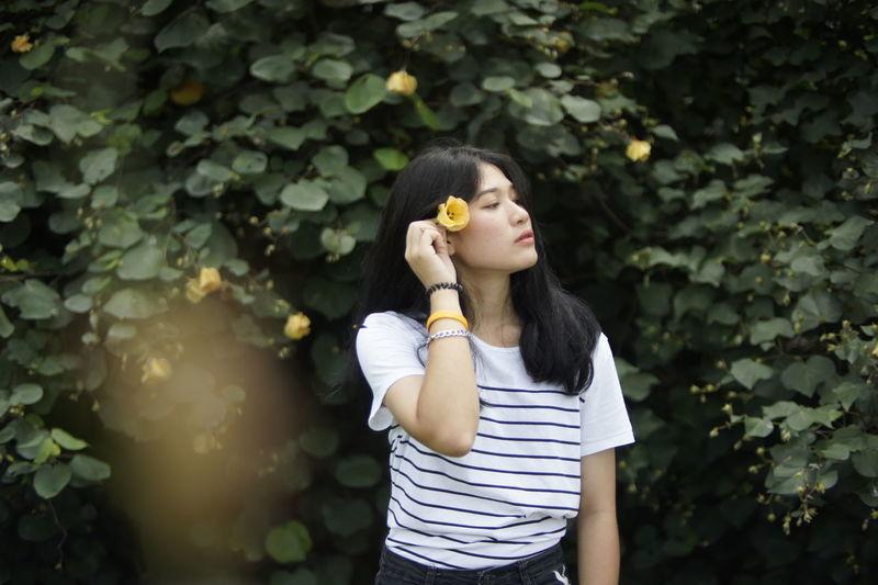 Woman wearing flowers standing against plants in park