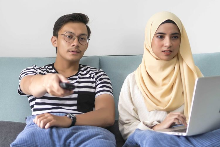 Young Malay Couple at the Sofa watching tv together holding the remote Sitting Front View Laptop Communication Wireless Technology Computer Technology Casual Clothing Connection Indoors  Using Laptop Two People People Three Quarter Length Men Lifestyles Real People Young Adult Togetherness Young Men Teenager