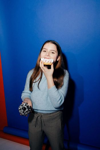 Portrait of smiling young woman eating food