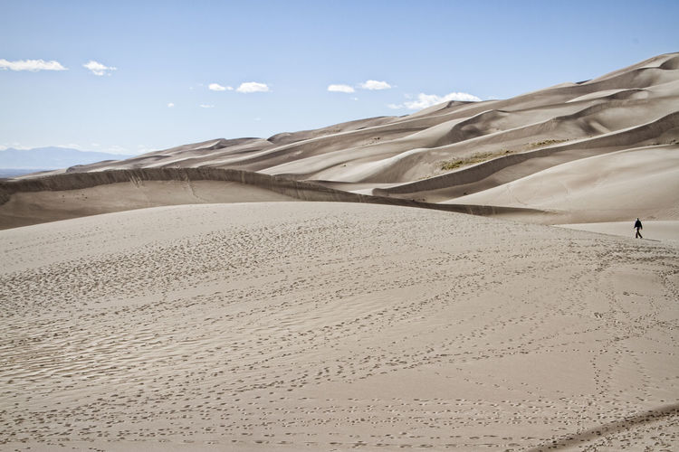 Man walking in great sand dunes national park and preserve against sky
