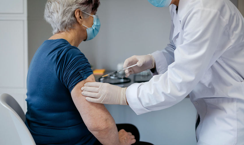 Midsection of doctor injecting patient in hospital