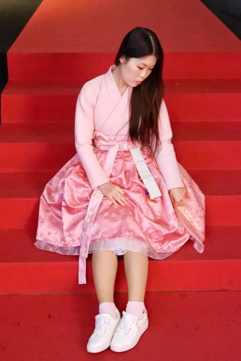 Full length of young woman sitting in pink dress on red steps