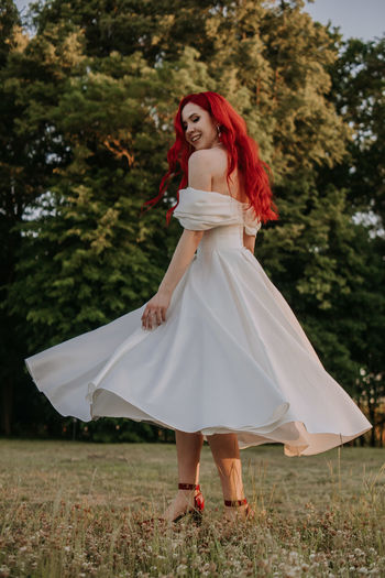 Wedding day. happy bride with redhead whirling and laughing in the park