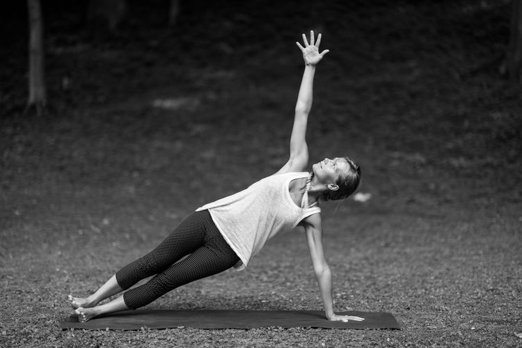 Young Woman Stretching At Park