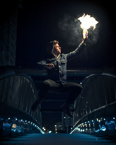 Flame hand on the bridge HUAWEI Photo Award: After Dark Architecture Arts Culture And Entertainment Built Structure Casual Clothing City Full Length Illuminated Leisure Activity Lifestyles Low Angle View Men Motion Night One Person Performance Real People Skill  Stage Transportation Young Adult