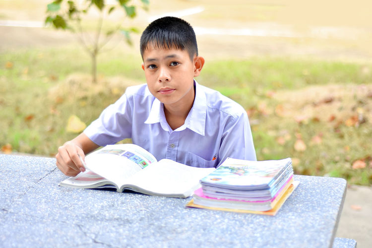 Portrait Of Boy Reading Book While Studying At Park