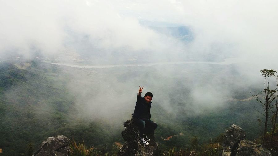 High angle view of man gesturing peace sign while sitting on rock at cliff against mountains during foggy weather