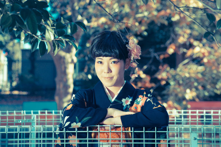Portrait Of Beautiful Japanese Woman With Arms Crossed In Park