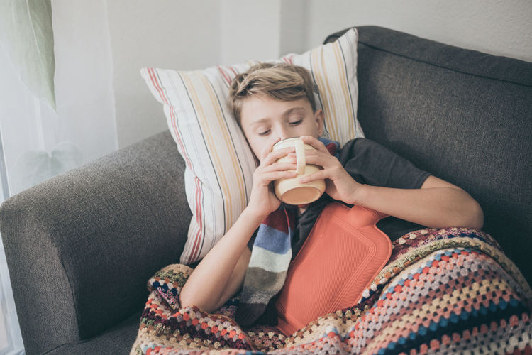 Ill boy having coffee while relaxing on sofa at home