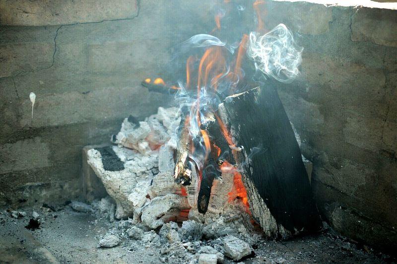 Firewood burning in corner of walls
