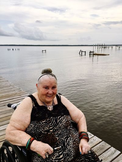 Portrait of smiling disabled woman on wheelchair by sea against cloudy sky