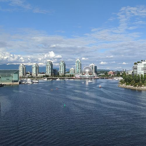View of city by river against sky