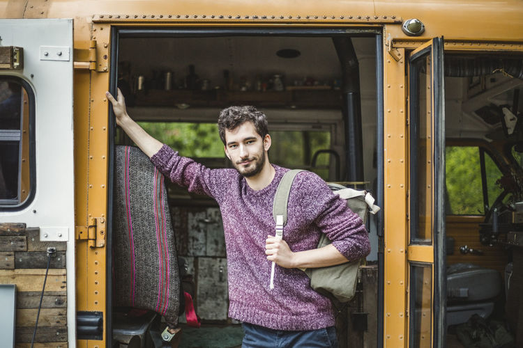 Portrait of young man standing at bus