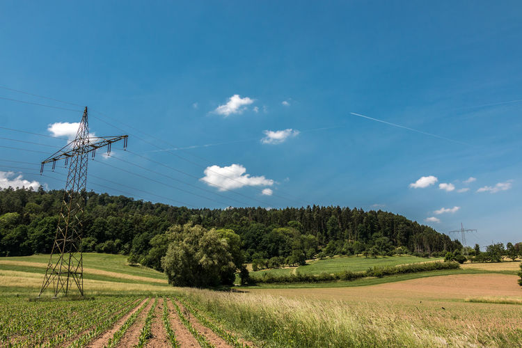 Power pylon in the German countryside with forests, fields and meadows Beauty In Nature Cable Cloud - Sky Day Electricity  Environment Field Green Color Growth Land Landscape Nature No People Plant Power Supply Scenics - Nature Sky Technology Telephone Line Tranquil Scene Tranquility Tree Vapor Trail
