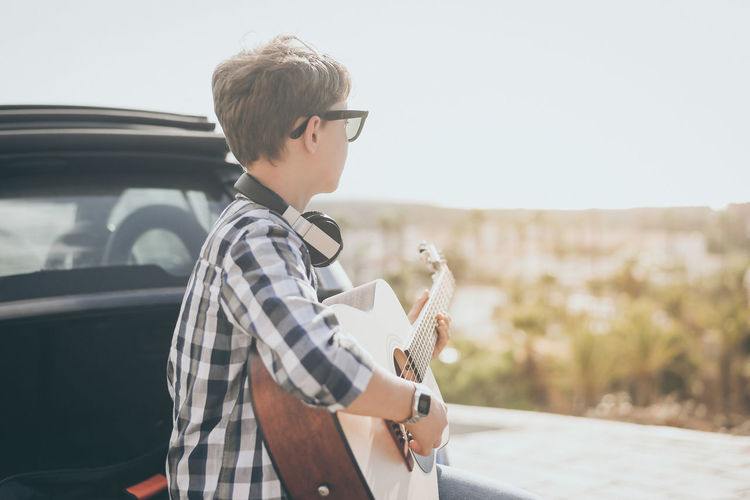 Young boy playing guitar and using smartphone outdoor. teen enjoying music