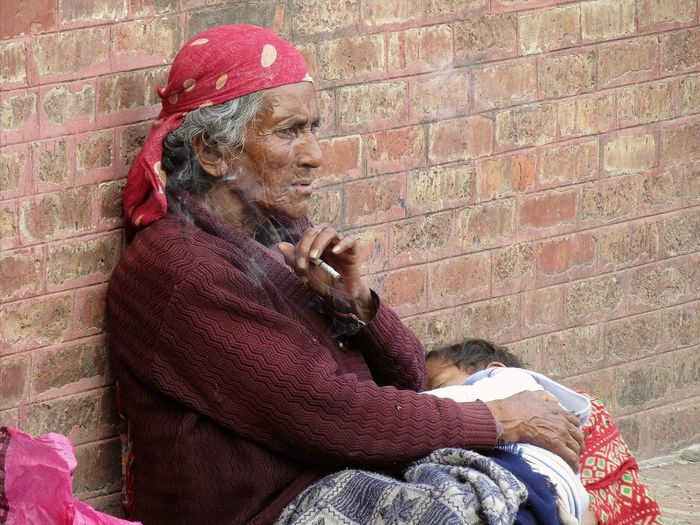 Elderly Woman smoking Smoking Cigarette Holding Baby Red Sitting Brick Wall Architecture