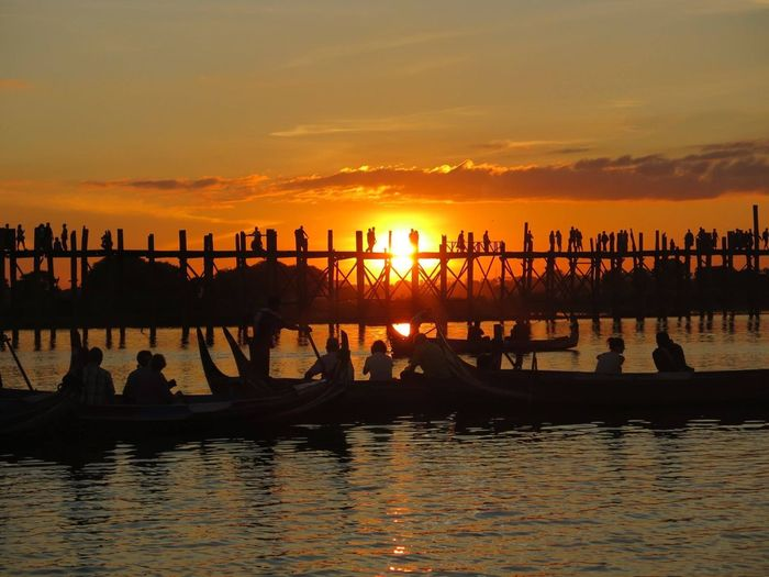People on boat in river by u bein bridge against sky during sunset