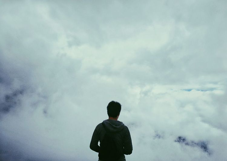 Rear View Of Man Standing Against Cloudy Sky