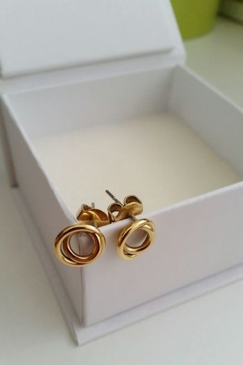 High Angle View Of Gold Earrings On White Box