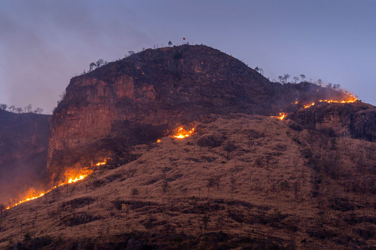 Forest fire on mountains. Mountain Sky Architecture Nature No People Land Building Exterior Rock Built Structure Outdoors Illuminated Night Low Angle View Building Scenics - Nature Environment History The Past Solid Travel Destinations Formation
