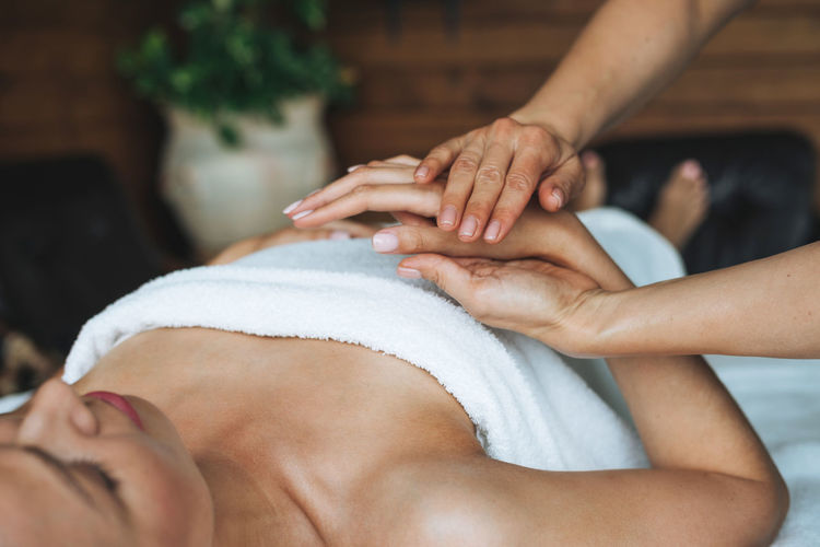 Midsection of woman lying on hand