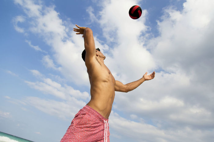 Fitness guy having fun playing volleyball in a sunny day at the beach Action Ball Beach Beach Life Blue Competition Excercise Fitness Freedom Fun Guy Handsome Man Hollidays Low Angle View Man Nature Outdoors Playing Runing Sky Sport Summer Vacations Volley Ball Volleyball