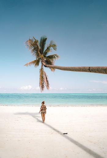 Woman walking under palm tree