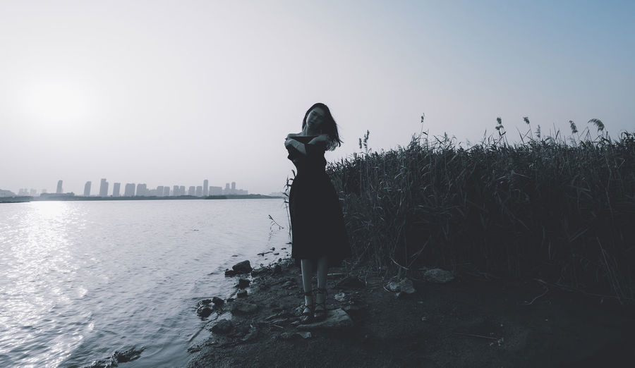 Side view of woman standing on shore against sky