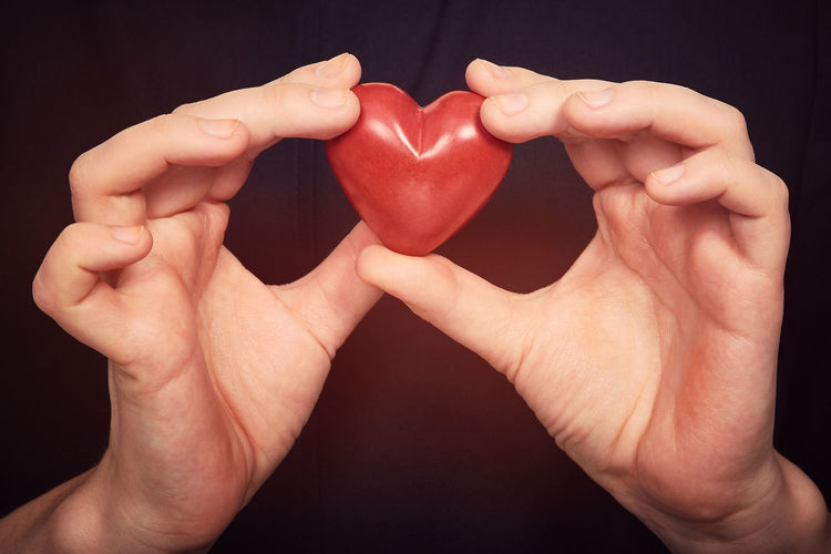Close-up of hands holding heart shape against black background