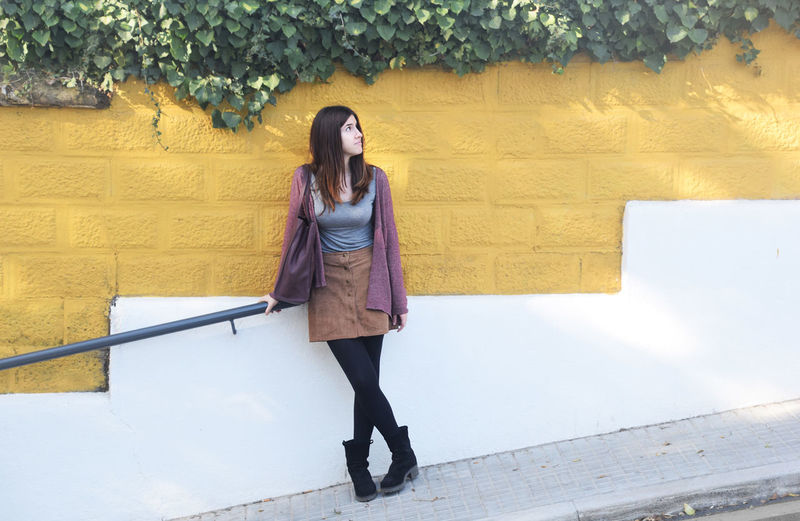 Full length of young woman looking up while standing against wall