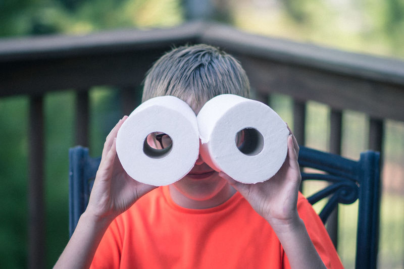 Boy Looking Through Toilet Papers