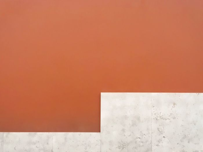 Orange wall with marbled stone on the bottom. The Graphic City Exterior Lines Orange Abstract Architecture Building Building Exterior Built Structure Close-up Copy Space Day Geometric Shape Geometry Lines And Shapes Marble Marbledstone No People Orange Color Outdoors Outside Stone Wall - Building Feature White Color