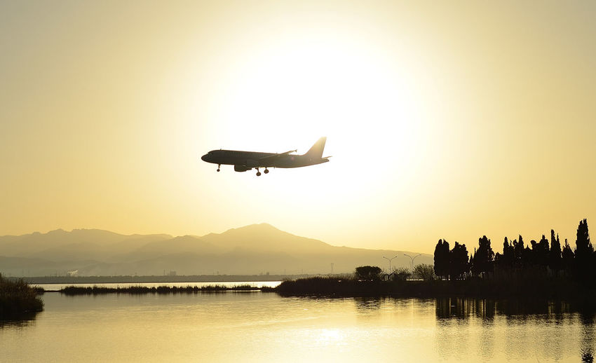 Sky Water Flying Transportation Sunset Silhouette Airplane Mode Of Transportation Air Vehicle Orange Color Elmas Airport Elma Sardinia Waterfront No People Nature
