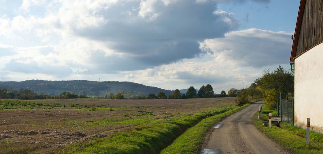 Panoramic shot of road amidst field against sky