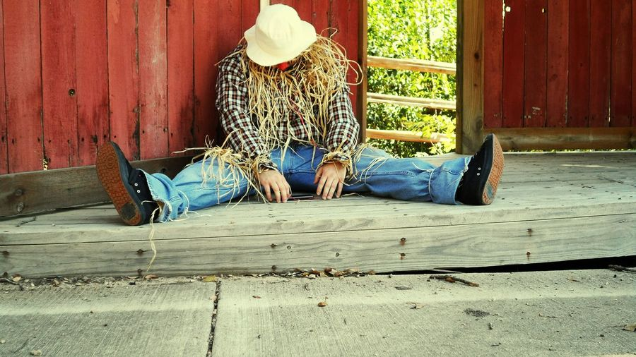 Full Length Of Man Imitating Scarecrow At Farm