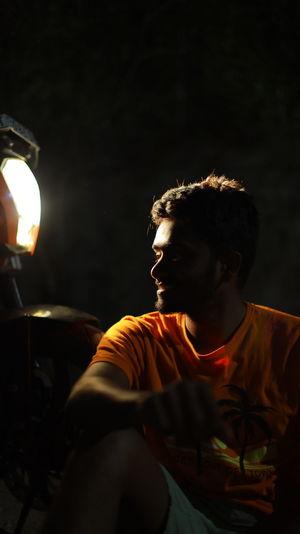 Man looking away while sitting at illuminated night