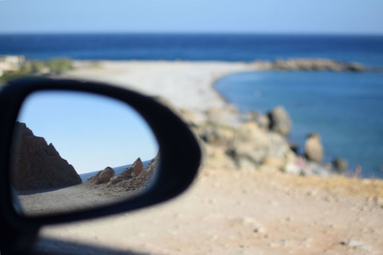 Artistic shot of Gialiskari beach in Crete Artistic Beach Beachphotography Beauty In Nature Blue Car Clear Sky Close-up Day Greece Horizon Land Nature No People Outdoors Reflection Rock - Object Scenics - Nature Sea Selective Focus Side-view Mirror Sky Sunlight Transportation Water