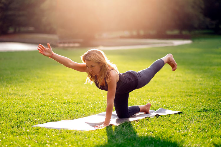 Photo in backlight of woman doing yoga alone outdoor at the park at sunset