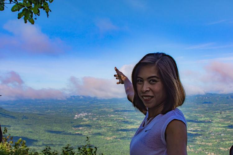 Portrait Of Smiling Woman On Landscape Against Sky