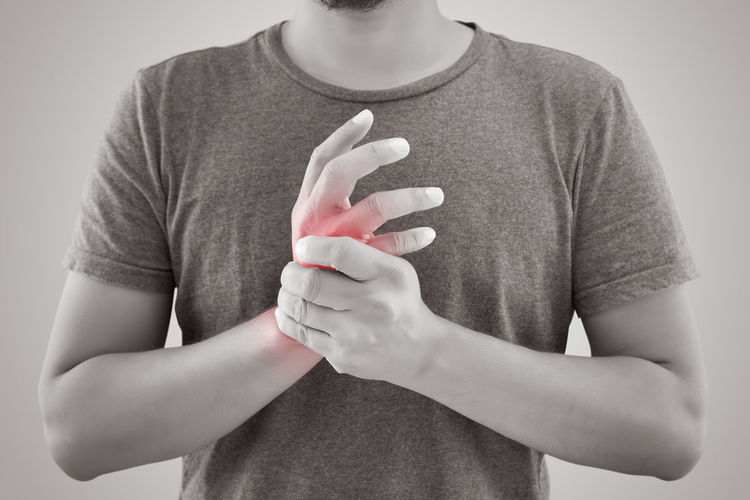 Midsection Of Man With Wrist Pain Standing Against Gray Background