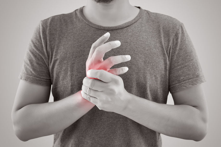 Asian man with pain in wrist against gray background Man Pain RheumatoidArthritis Swelling Ache Arthritis Condition Dislocation Hand Numbness Osteoarthritis Rheumatic Sprained Wrist