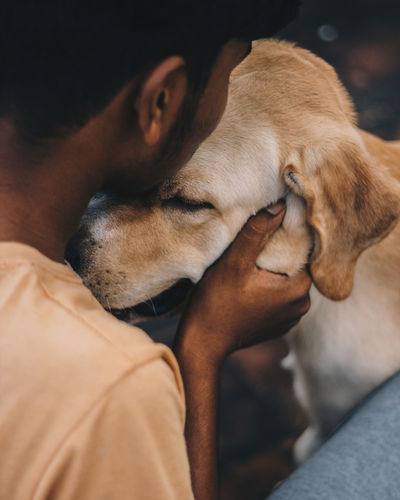 Close-up of man embracing with dog outdoors